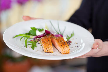 Cropped image of waitress displaying salmon dish in restaurant-2